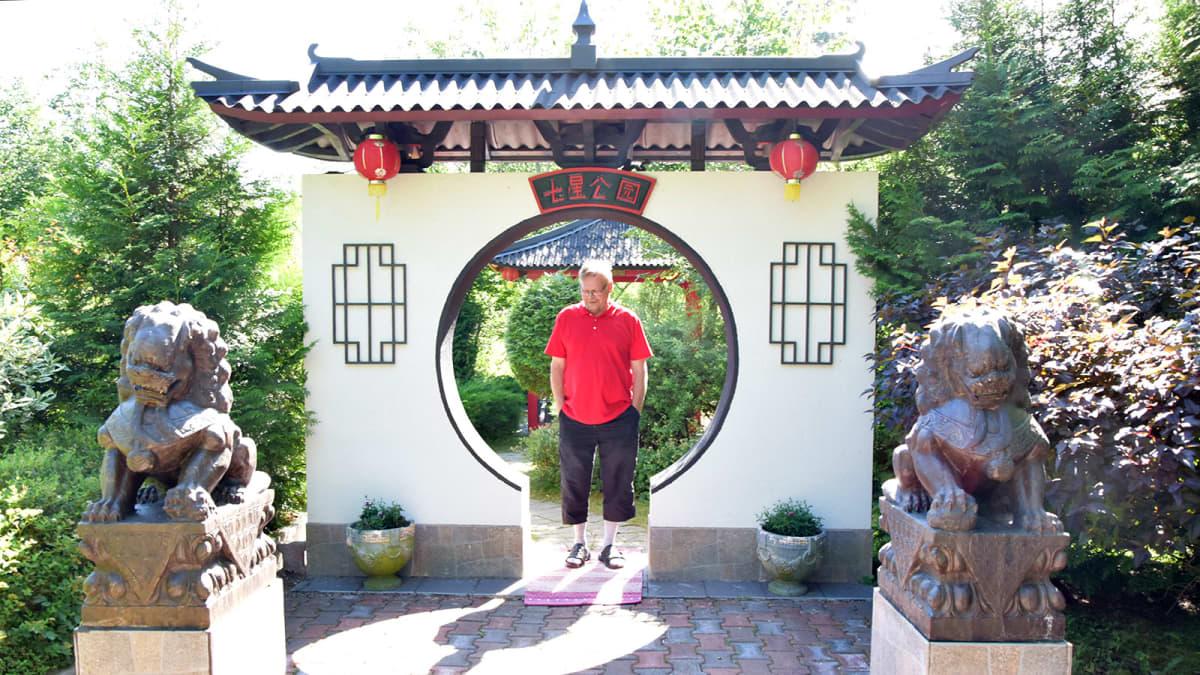 Hämeestä löytyvät kiinalaisen puutarhan kuuportti, jonka suuaukossa seisoo mies