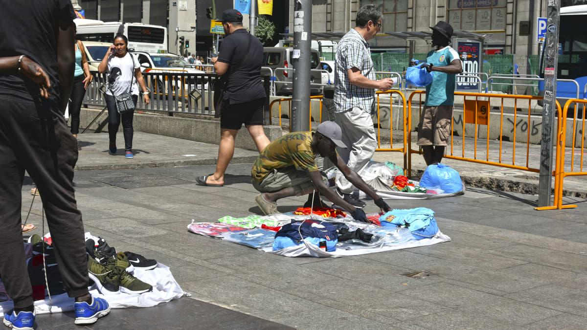 """Senegalilainen """"Papi"""" asettelee kauppatavaroitaan kadulle."""
