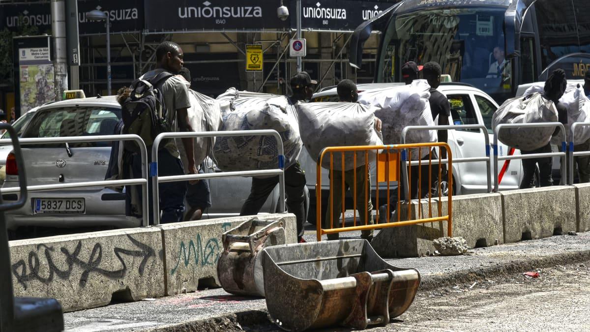 Poliisin takia myyntipaikkaa vaihtavia afrikkalaisia katukaupustelijoita liikenteen seassa Madridin keskustassa.