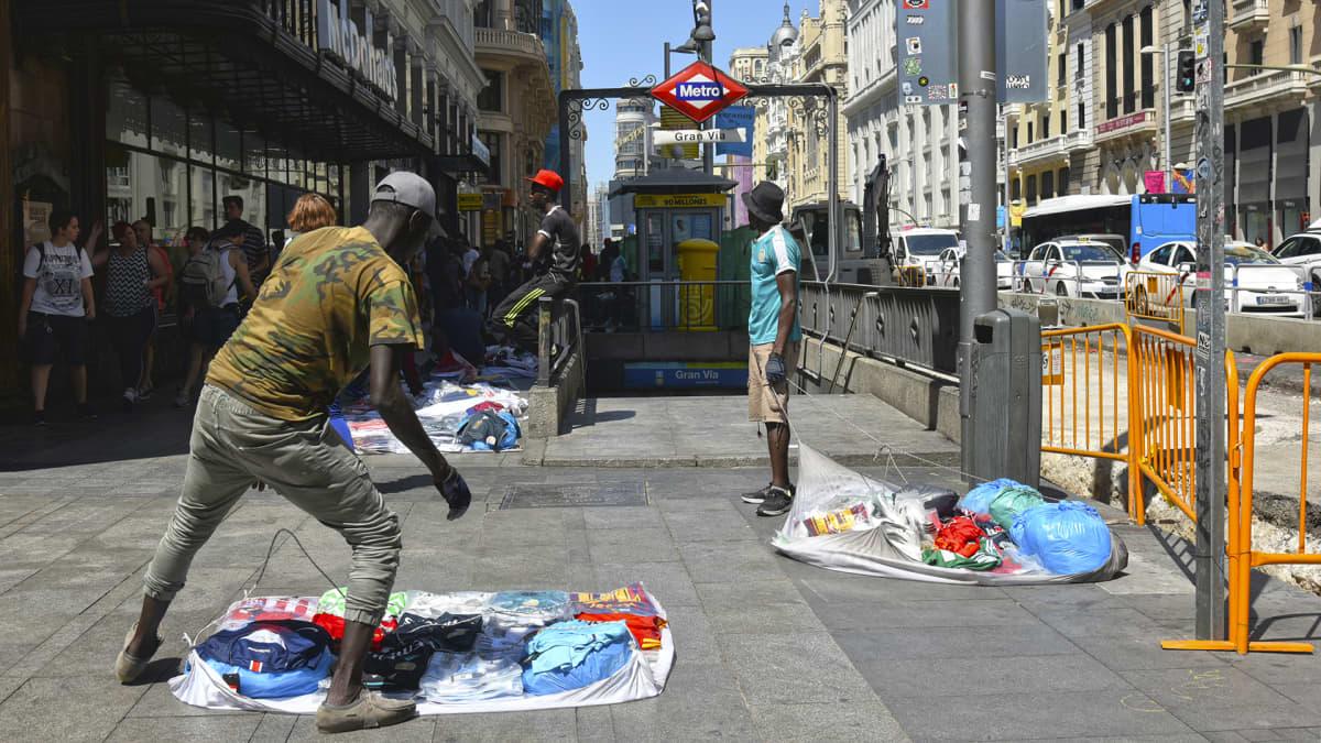 Afrikkalaisia kaupustelijoita on Espanjan kaupunkien kaduilla tuhansittain. Heillä on myynnissä mm. lenkkitossuja, jalkapalloseurojen paitoja, muotilaukkuja, huiveja, kosmetiikkaa, koruja. Hinnat ovat edulliset, mutta tuotteiden alkuperää myyjät eivät kerro.