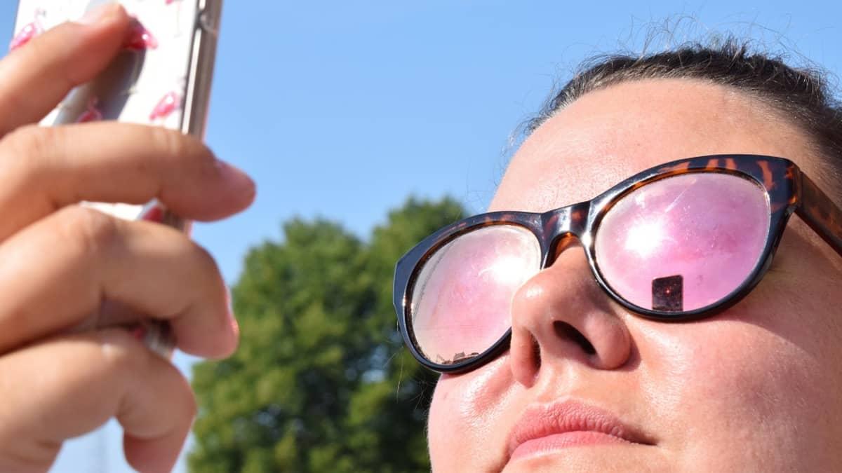 Nainen katsoo kännykkää aurinkoisena kesäpäivänä.