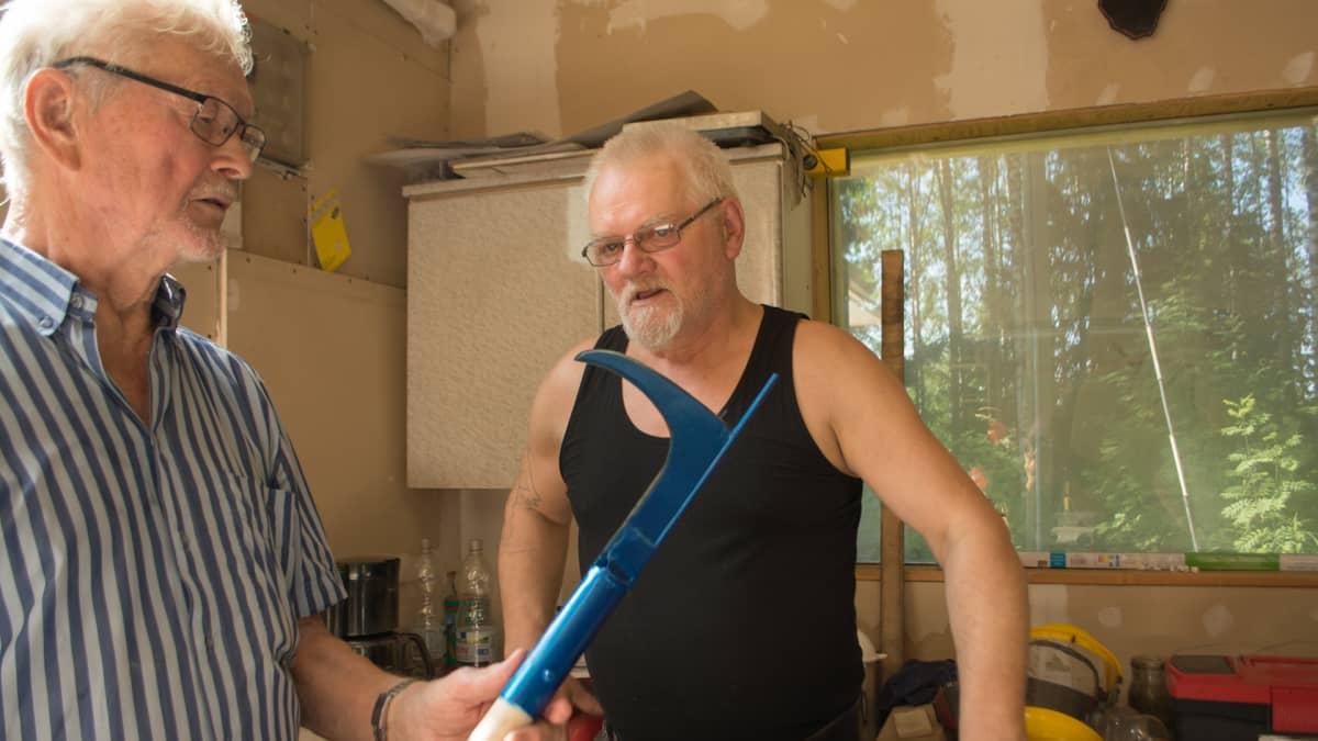 Yrittäjä Richard Herzog (oik.) tutkii raivausveistä yhdessä keksijä Eino Korhosen kanssa.