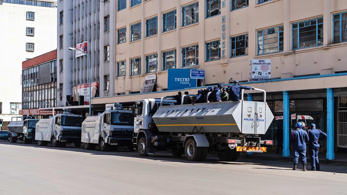 Mellakkapoliisit ja vesitykit oppositiopuolue MDC:n päämajan ulkopuolella.