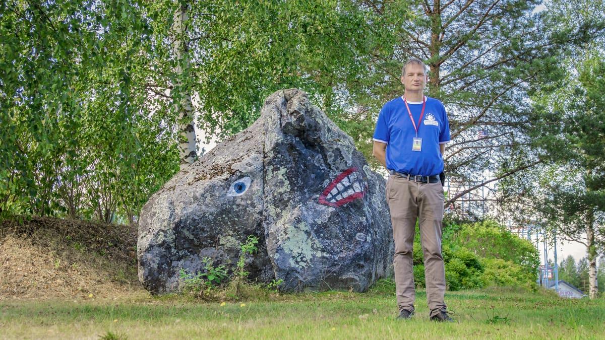 Mies seisoo kiven edessä