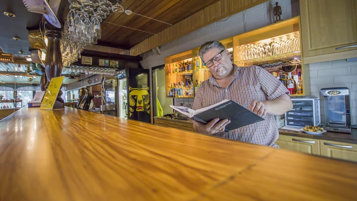 Juha Willman tutkailee ravintolan mappeja.