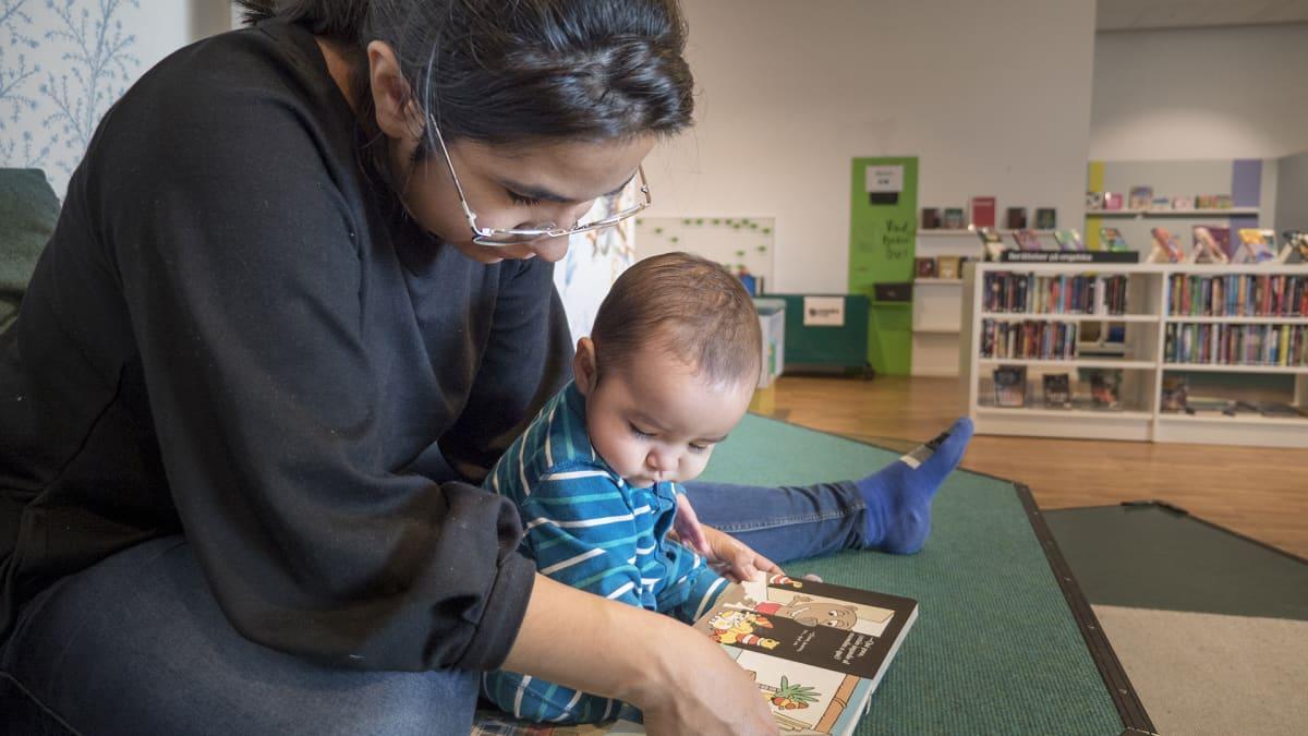 Ninel Barrios Pizarro lukee kirjaa lapselleen.
