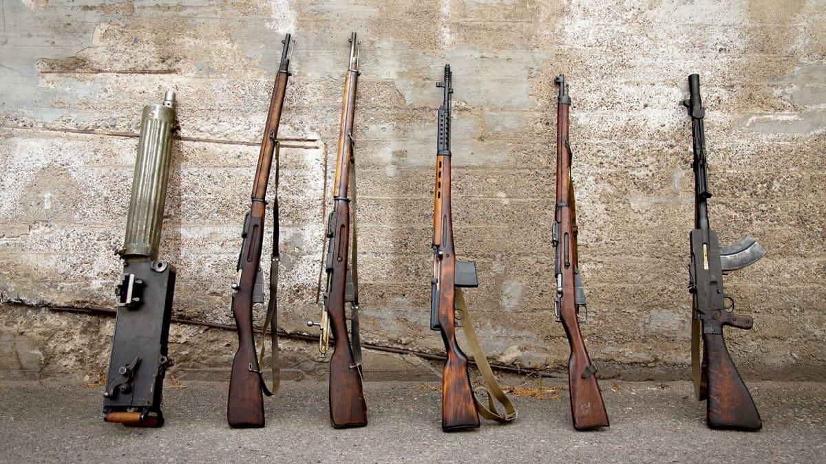 Vanhoja aseita seinää vasten pystyssä.