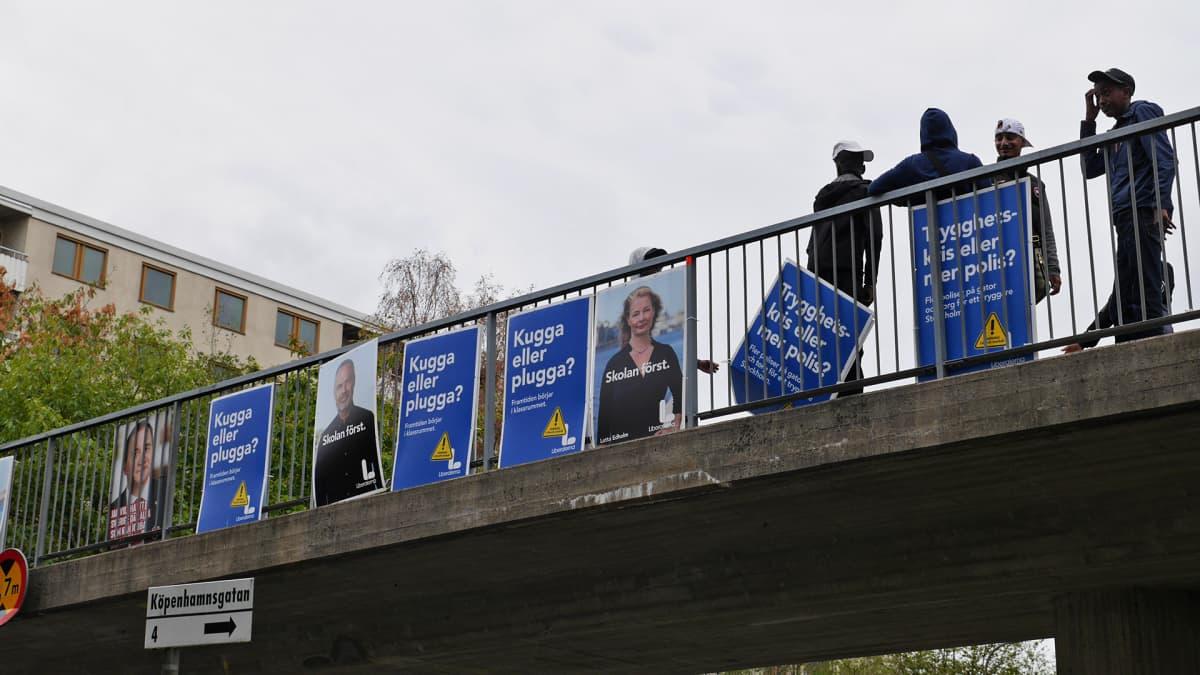 Ihmisiä kylttien kanssa sillalla.
