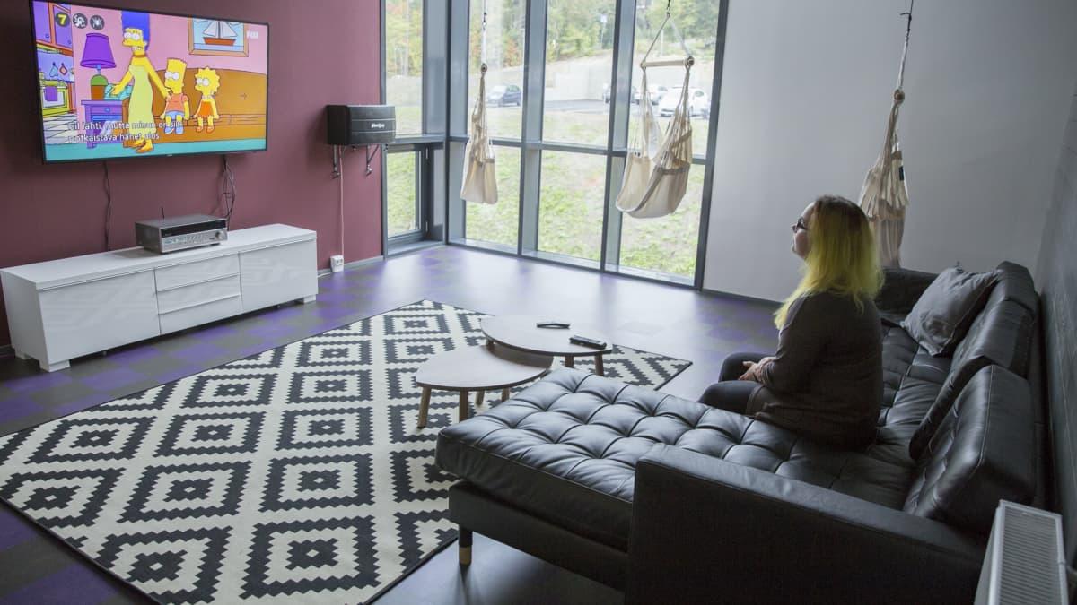 Linda Jeskanen katsoo televisiota opiskelija-asuntolansa yhteistiloissa.