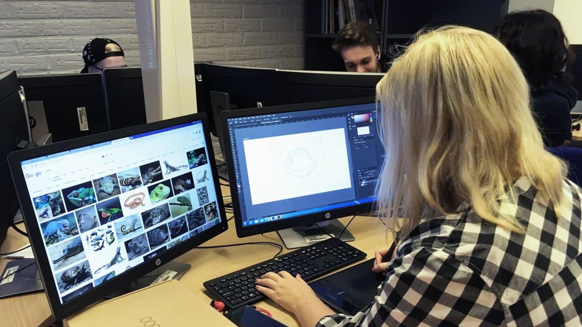 tyttö istuu tietokoneella koulussa