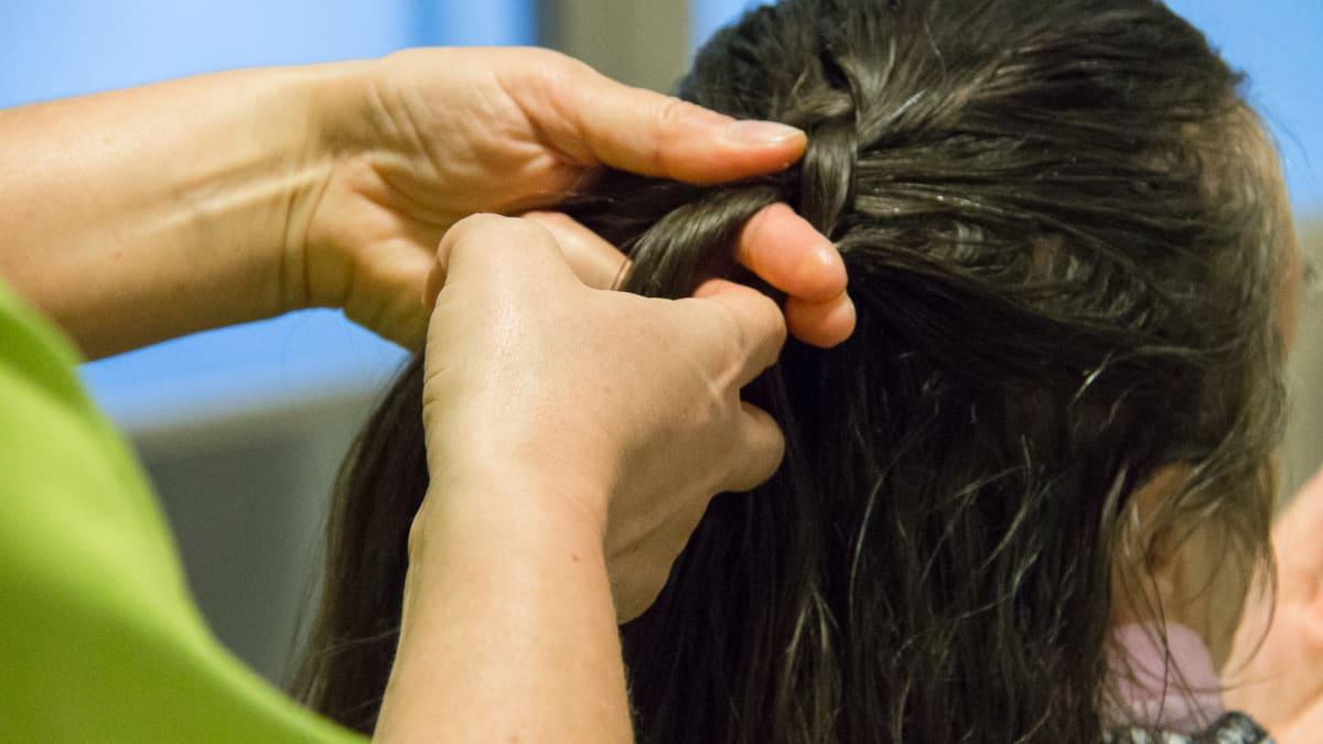 Muistisairaan vanhuksen hiuksia letitetään palvelutalossa.