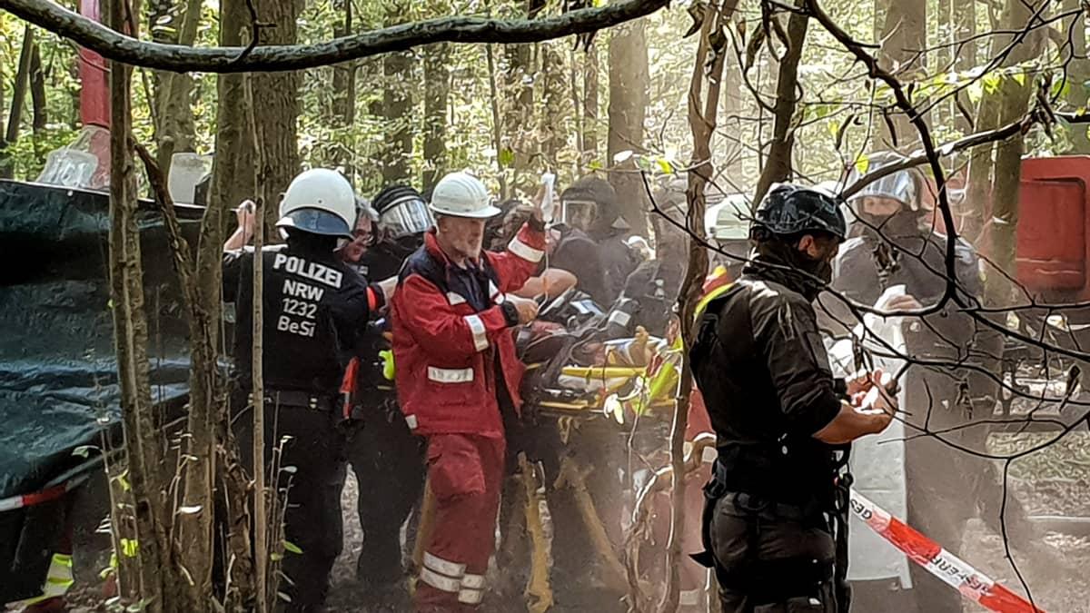 Poliiseja ja ambulanssihenkilökunta auttavat metsässä loukkaantunutta
