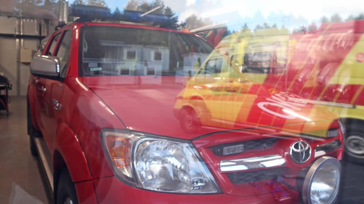 Hailuodon paloaseman johtoauto tallissa, ensivasteen sairasauto heijastuu ikkunasta.