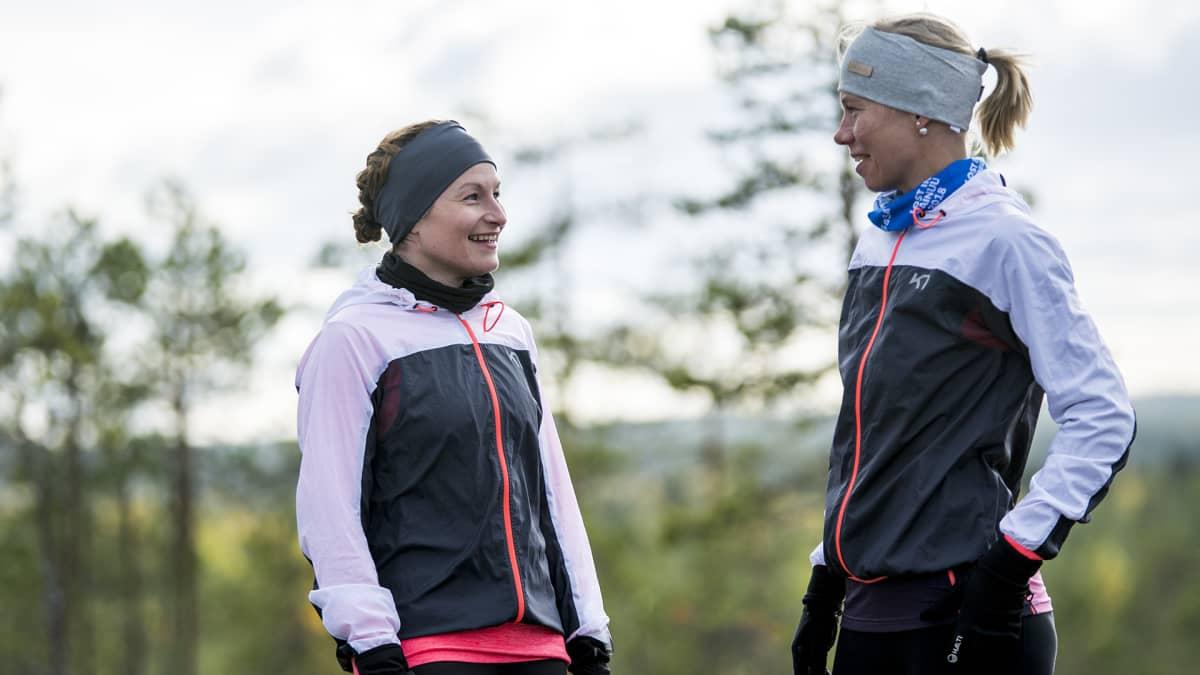Kaksi naista nauraa metsässä.