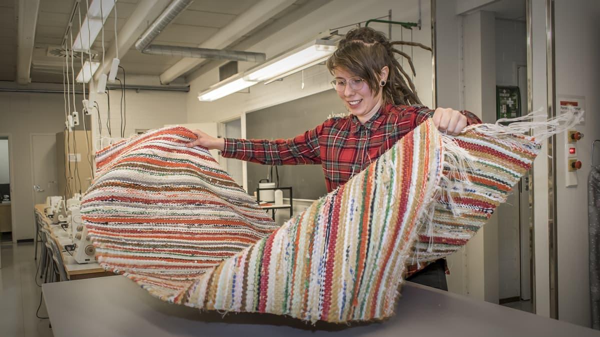 Nuori nainen esittelee kutomaansa mattoa
