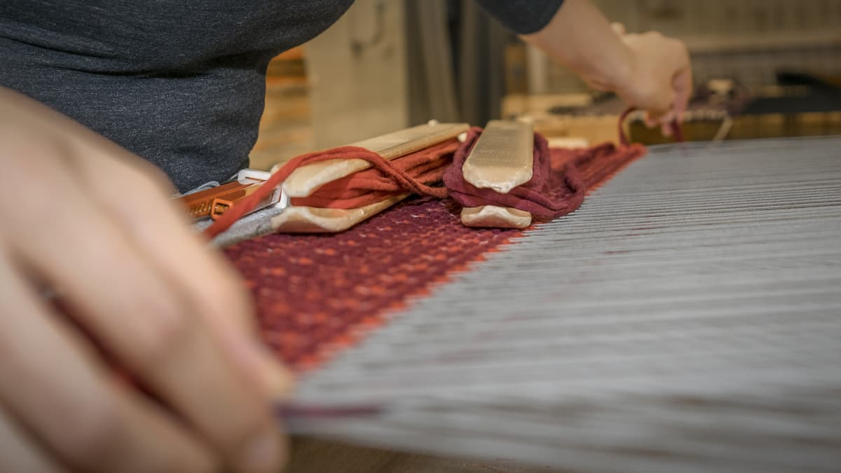 nainen kutoo mattoa