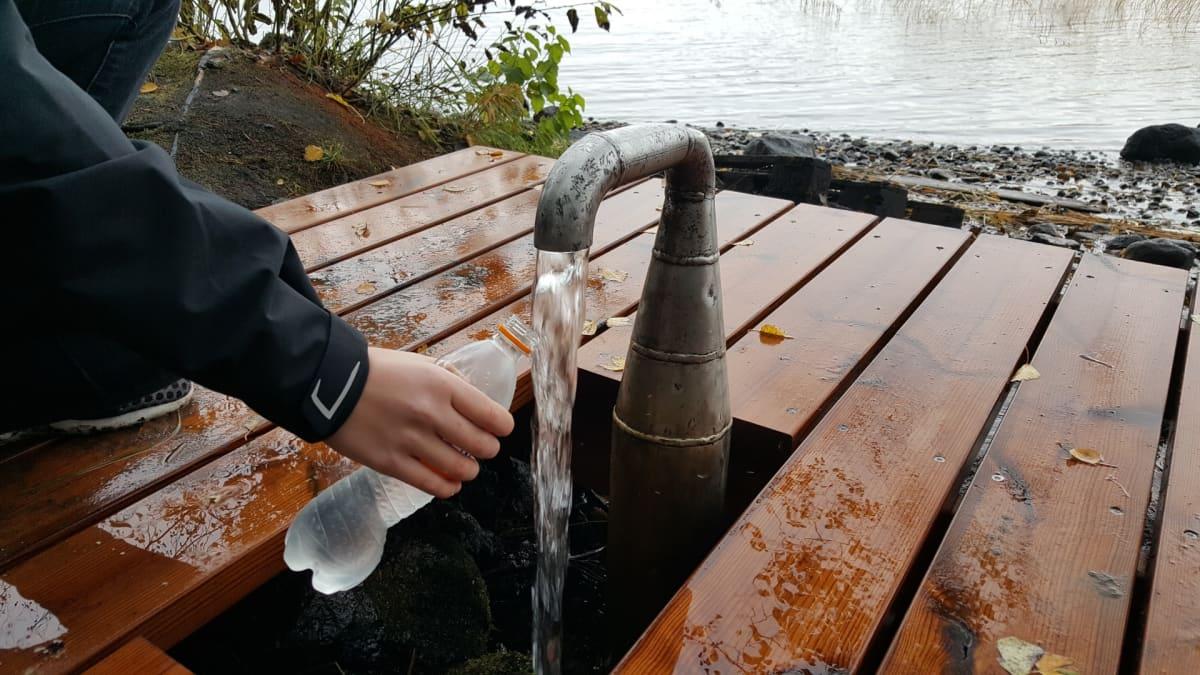 Henkilö ottaa vettä pulloon Lappeenrannan rantaraitin lähteeltä
