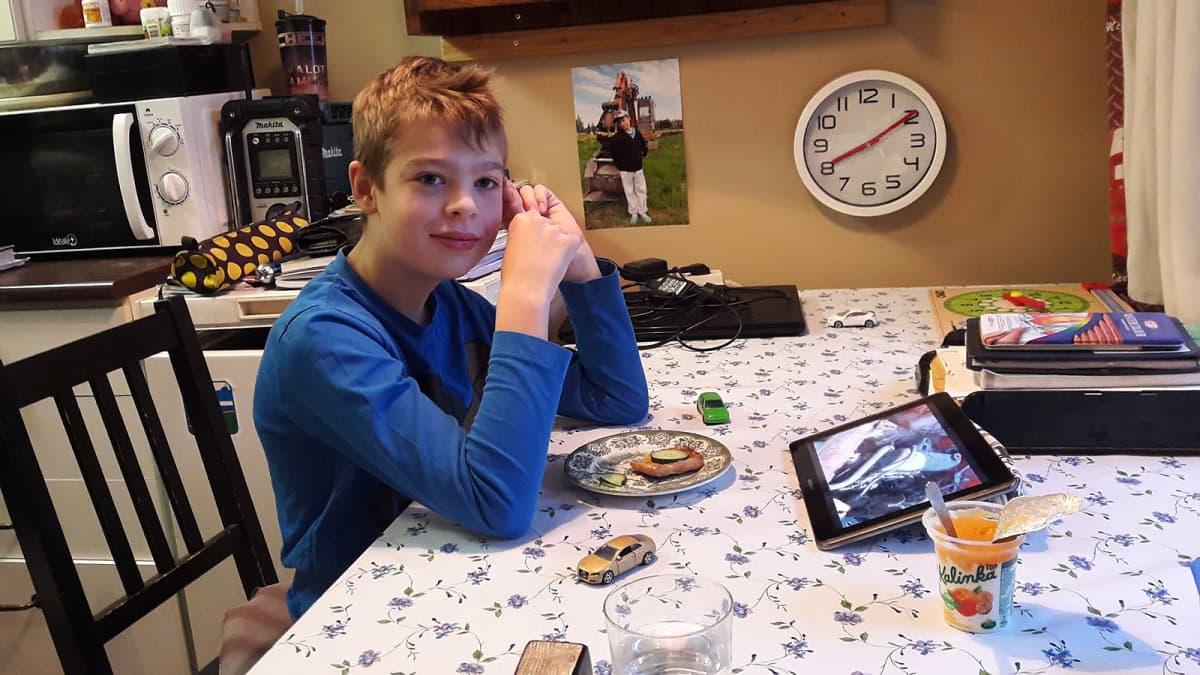 Kouluikäinen poika keittiön pöydän ääressä
