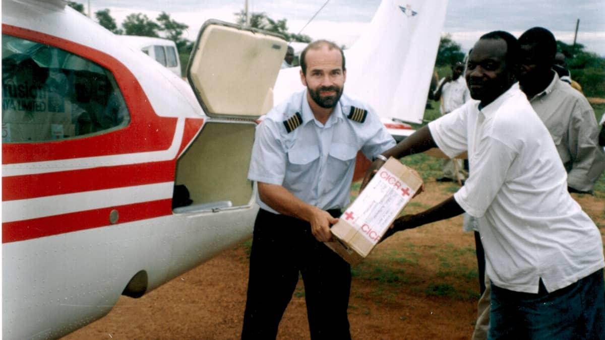 Janne Ropponen purkaa rahtia lentokoneesta ugandalaisen miehen kanssa.