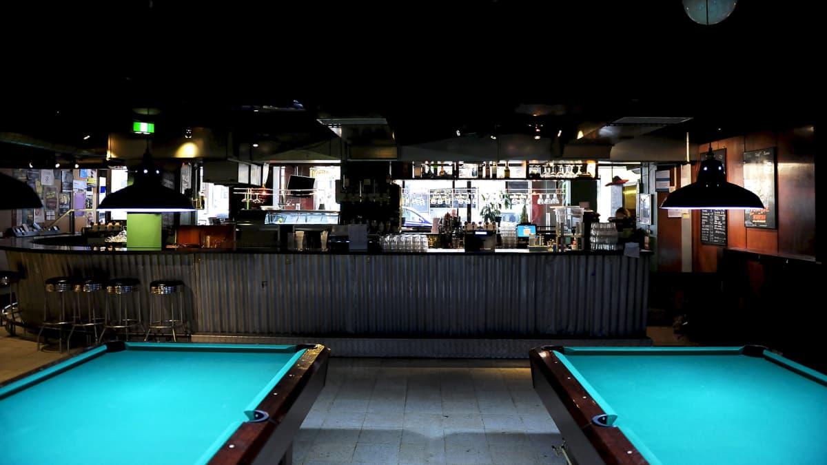 Biljardipöytiä ja baaritiski Corona-baarissa, joka sijaitsee Rakennusmestarien talossa.