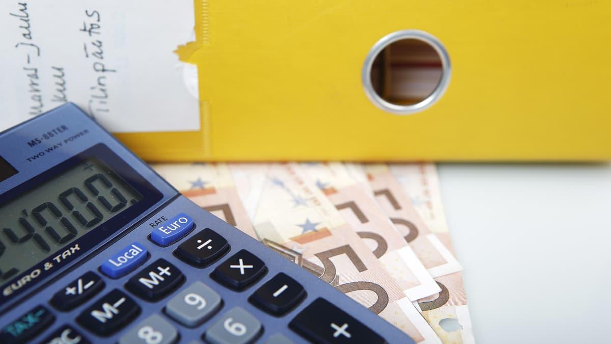 Kirjanpitomappi, rahaa ja laskin.