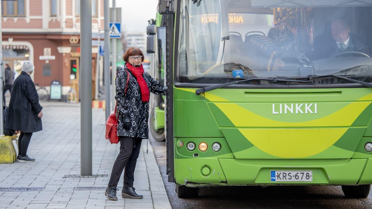 Nainen on astumassa linja-autoon.