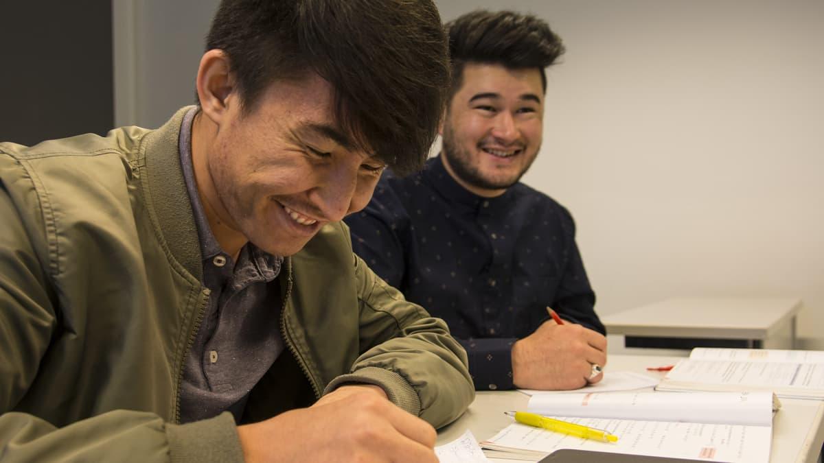 Oppilaat nauravat oppitunnilla.