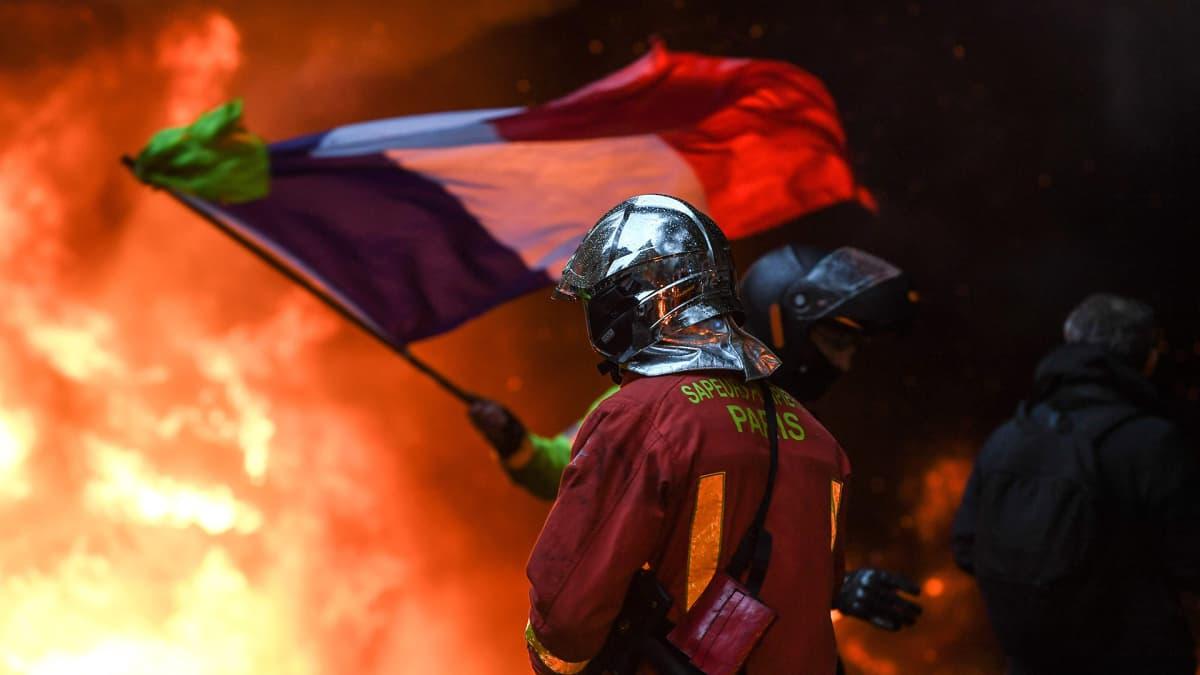 Pariisilainen palomies  kävelee kohti liekkejä ja taustalla hallitusta vastustava mielenosoittaja heiluttaa ranskan lippua.