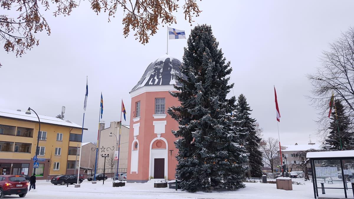 Vanha, punertava tornirakennus ja suuri kuusi Haminan torin nurkalla. Ympärillä eri maiden lippuja.