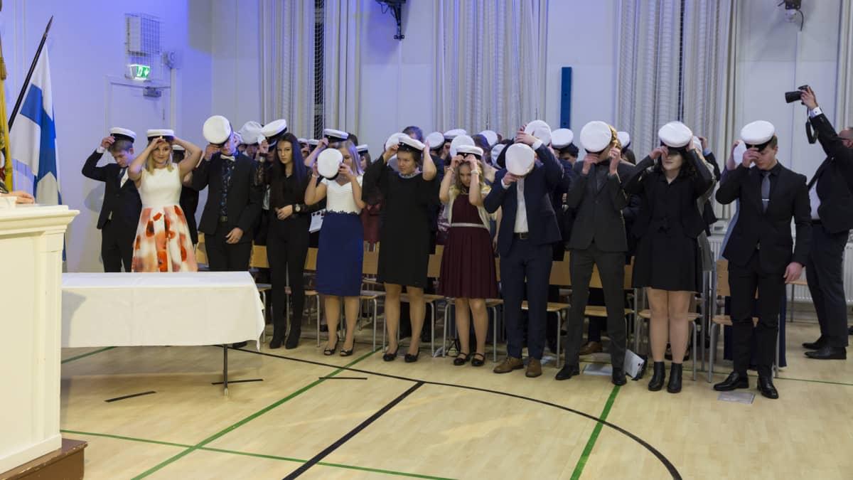 Uudet ylioppilaat laittavat valkolakit päähän