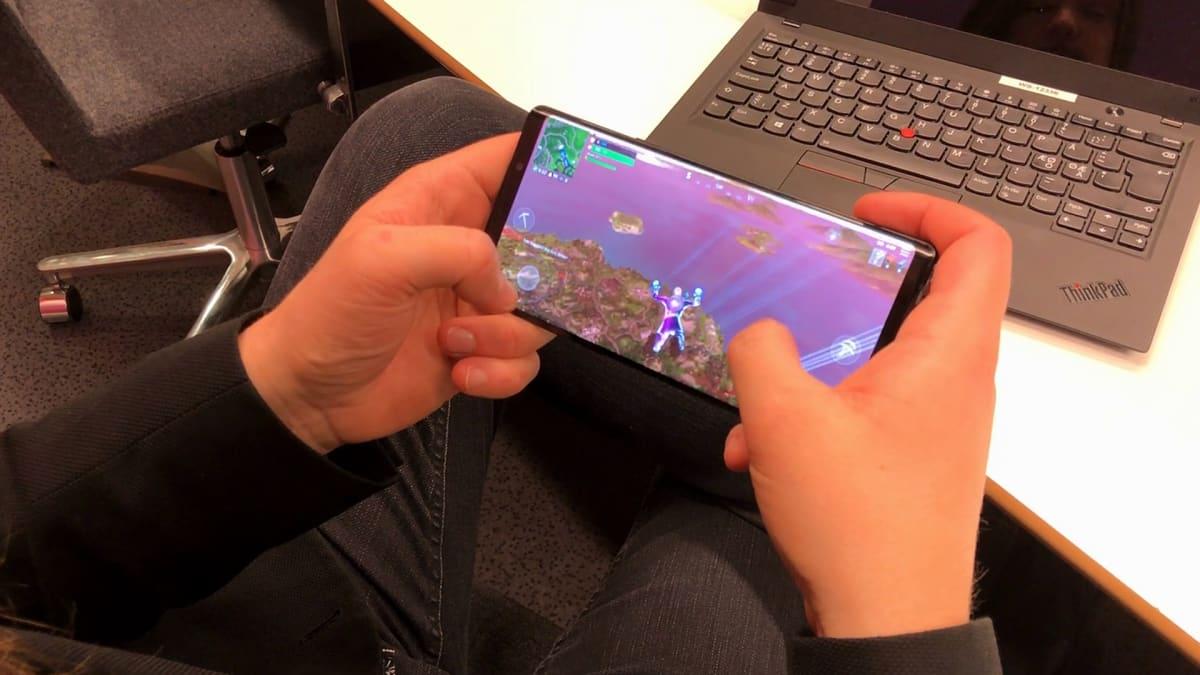 Kuvassa mies pelaa kännykällä Fortniteä