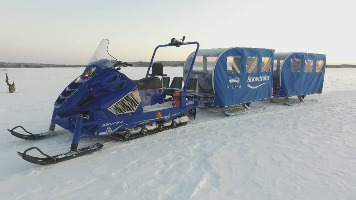 Apukassa jättikelkka on valjastettu vetämään lämmitettyjä kuljetusvaunuja.
