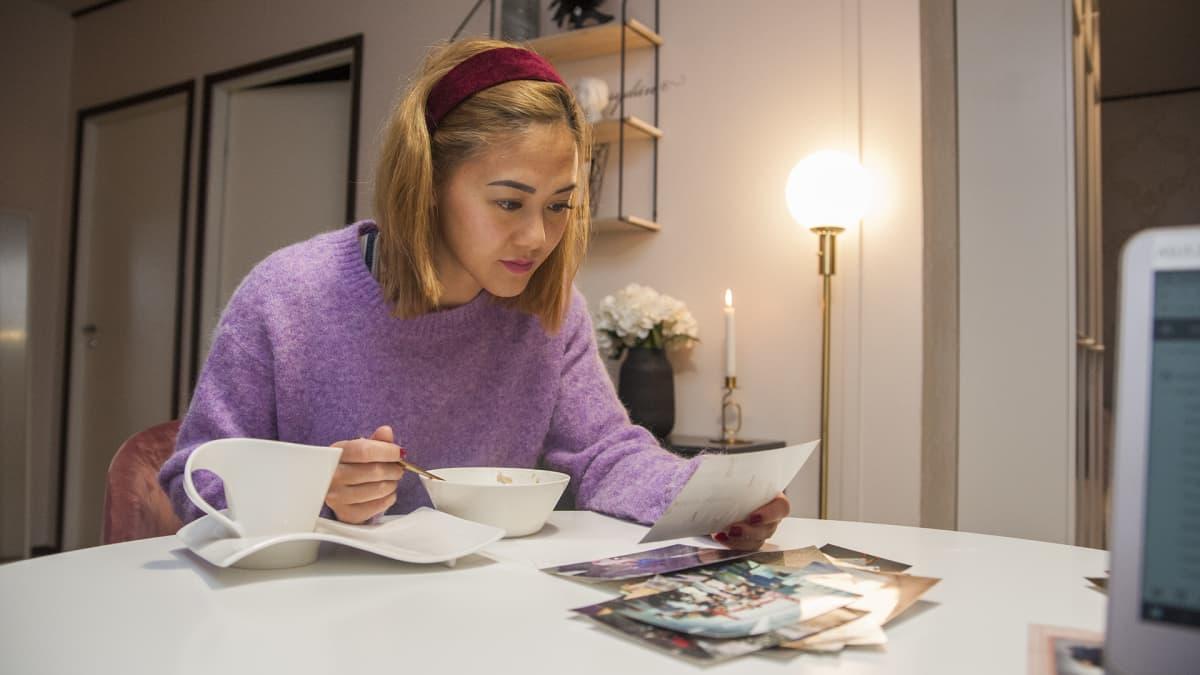 Nainen juo kahvia ja katsoo valokuvia
