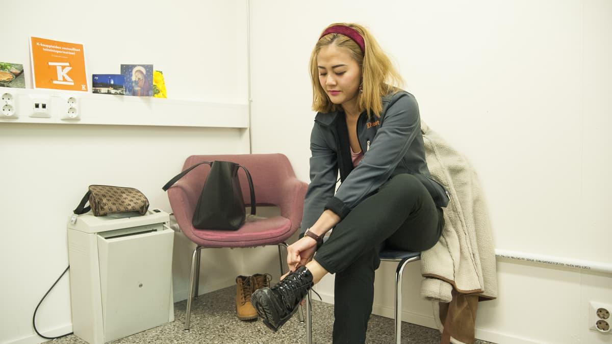 Nainen laittaa kengät jalkaan