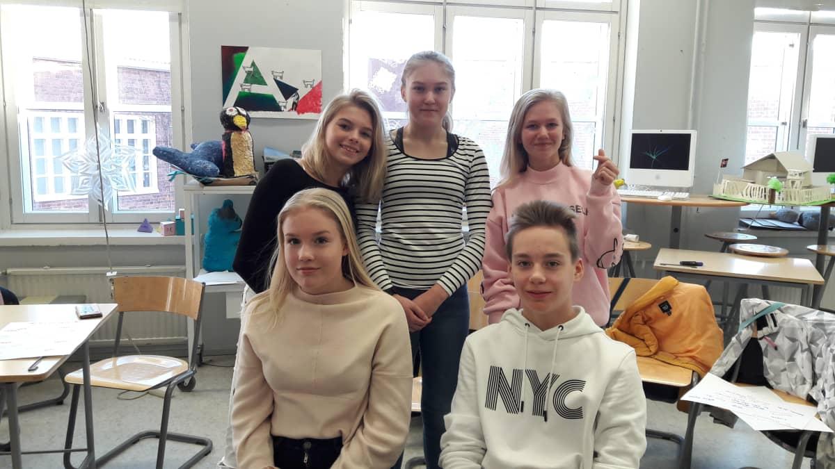 Viisi yläasteelaista nuorta ryhmäkuvassa kuvisluokassa. Neljä tyttöä ja yksi poika.