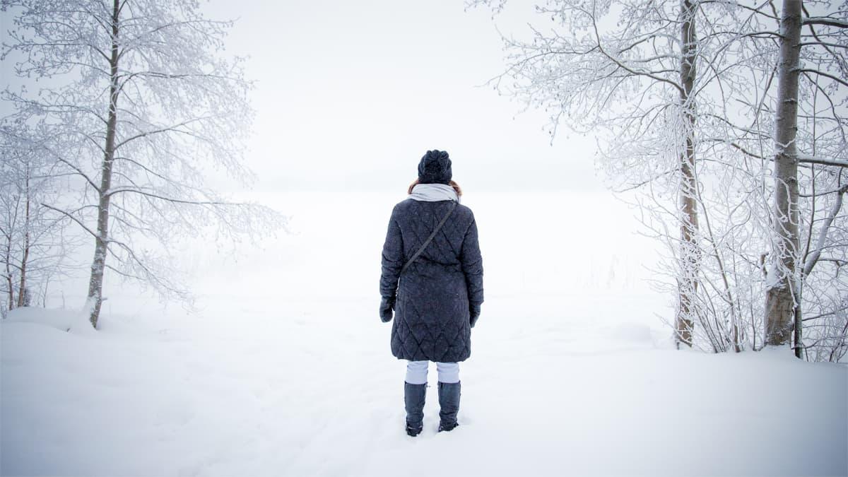 Nainen katsoo lumista maisemaa