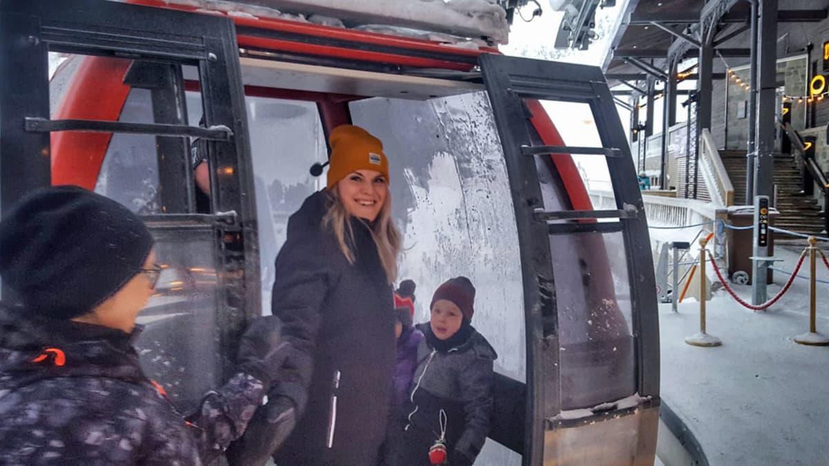 Nainen nousee lapsiensa kanssa gondoli-hissiin.