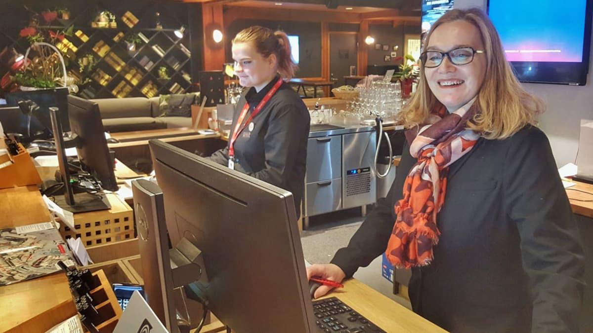 Kaksi hotellissa työskentelevää naista vastaanotossa.
