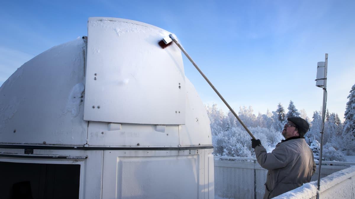 Mies harjaa observatorion luukusta lunta.