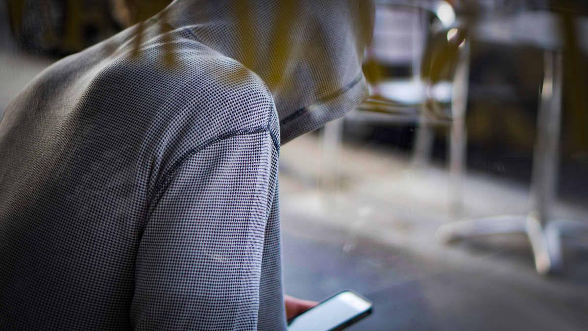 Huppariin pukeutunut mies kännykän kanssa.
