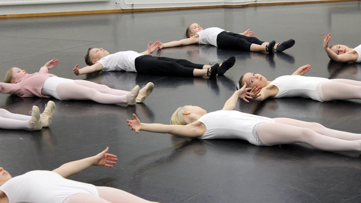 Nuoret balettitanssijat makaavat lattialla