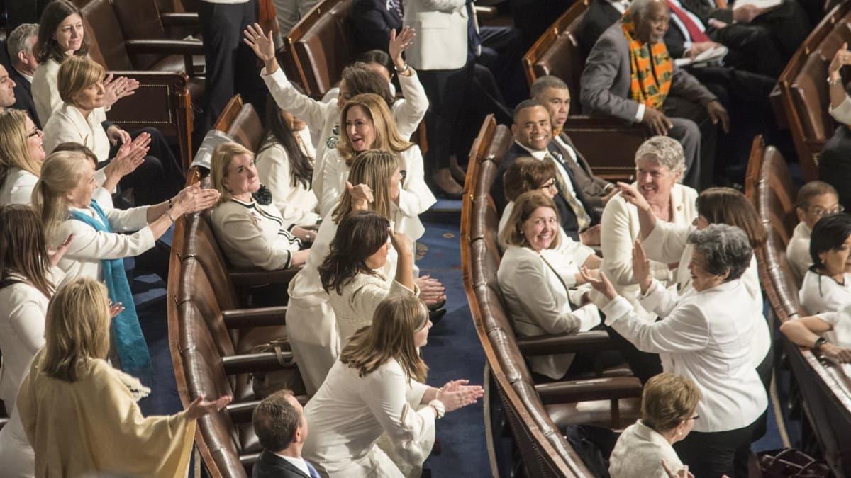 Valkoisiin pukeutuneita demokraattinaisia Kansakunnan tila- puheen yleisössä.