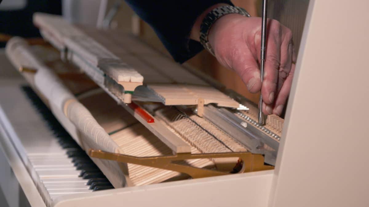 Pianonvirittäjä Pekka Savolainen huoltaa pianoa.