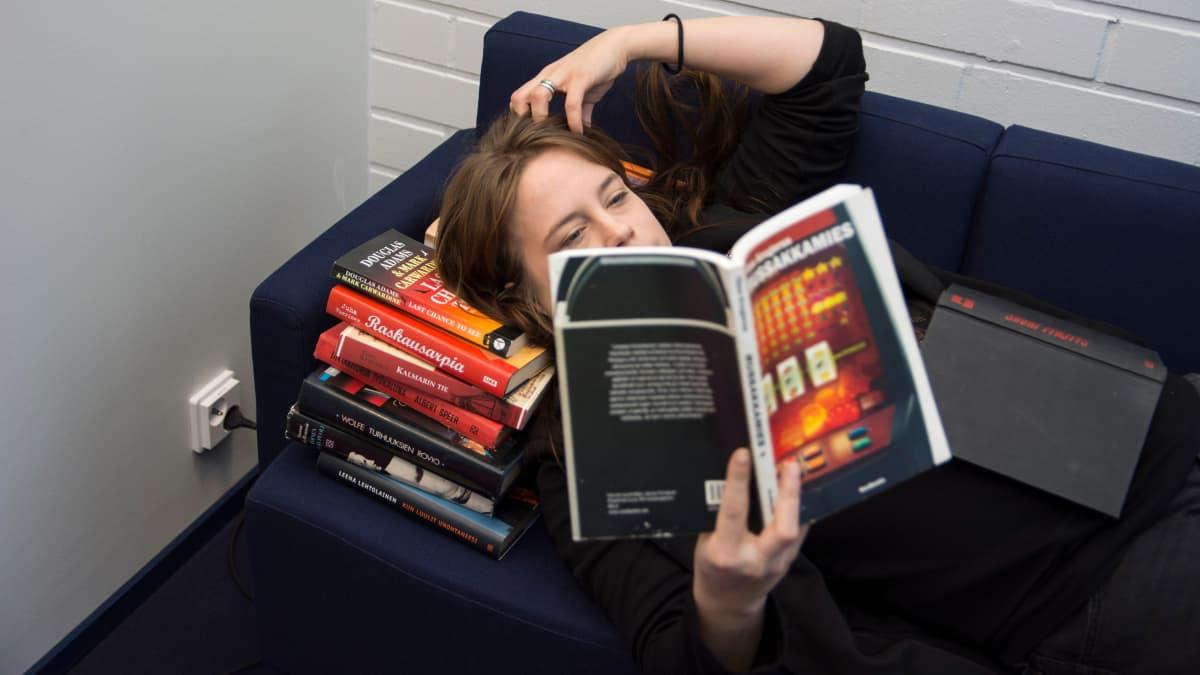 Nainen lukemassa sohvalla kirjapinon keskellä.