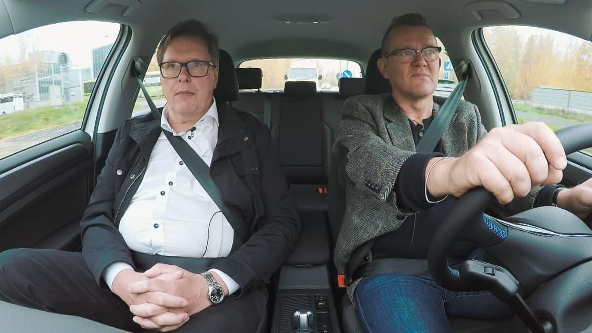 VTT:n liikenteen energia-asiantuntija Juhani Laurikko eGolfissa. Puoli seiskan toimittaja Matti Toivonen ohjaa.