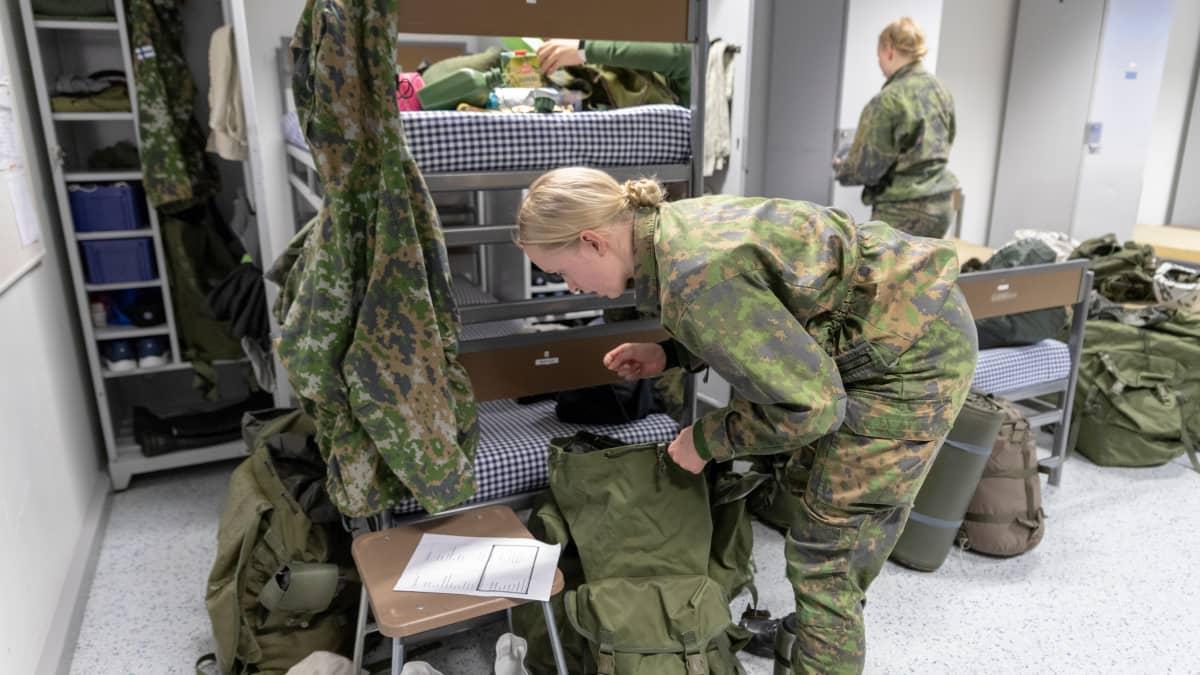 Vapaaehtoista asepalvelusta suorittava naisalokas pakkaa tuvassa reppua hiihtomarssia varten