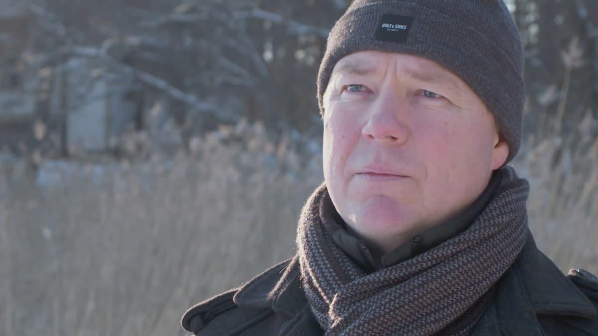 Pipopäinen mies talvisella rannalla.