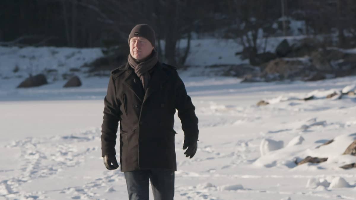 Mies kävelee lumisella rantajäällä.