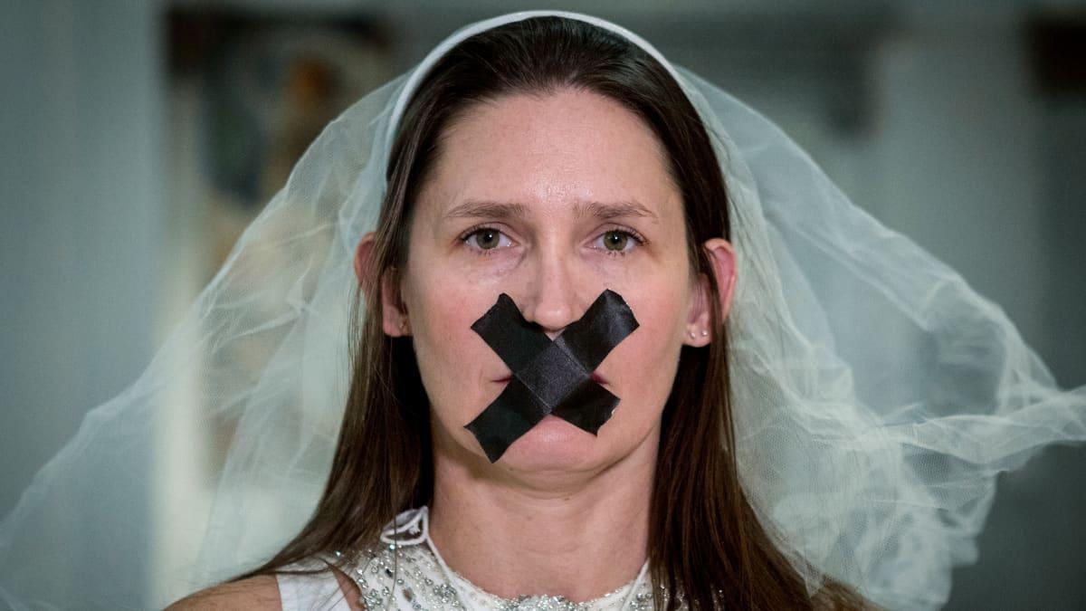 Kuvassa on nainen, jonka suu on teipattu kiinni.