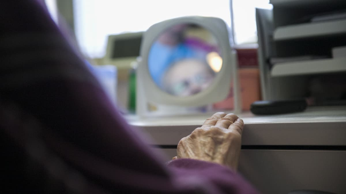 Vanhuksen käsi ja kasvot sumeina peilissä. Kuvassa Aini Mähönen hoivakodissa Tervossa.